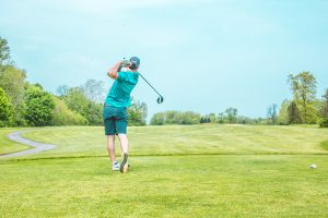 man positioned in golf swing
