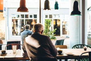 Elderly man sat in a cafe with a coffee