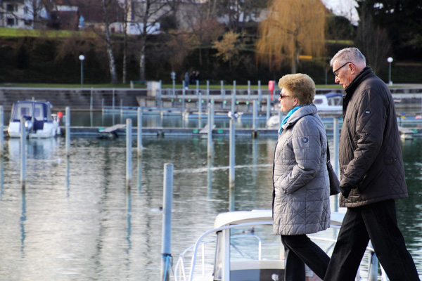 Elderly couple walking by lake